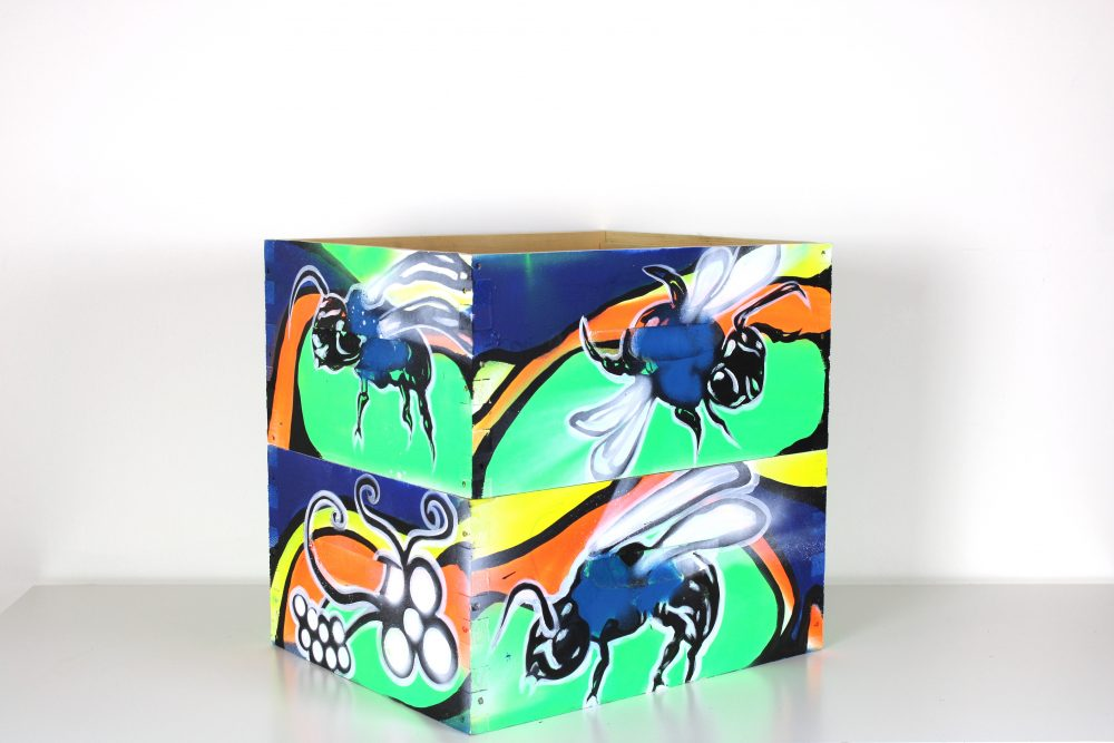 Wood hive box painted with blue bees against green, orange, yellow, and blue background.
